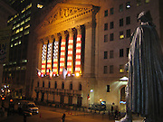 Statue of George Washington overlooking Wall Street and the New York Stock Exchange in New York, NY. Flag illumination at nighttime!