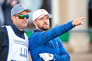 Justin Timberlake discusses the best line with his caddie before playing his opening tee shot during the third round of the Alfred Dunhill Links Championship European Tour at St Andrews, West Sands, Scotland on 28 September 2019.