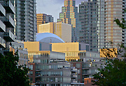 A skyline view of Toronto, looking through the dense condominium developement of harbourfront nieghbourhood, with the Rogers Centre visible  in the middle.