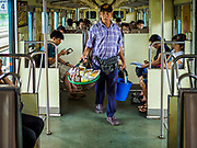31 MAY 2017 - CHACHOENGSAO, THAILAND:  A vendor walks the aisle of a Bangkok bound train at the train station in Chachoengsao, a provincial town about 50 miles and about an hour by train from Bangkok. The train from Chachoengsao to Bangkok takes a little over an hour but traffic on the roads is so bad that the same drive can take two to three hours. Thousands of Thais live outside of Bangkok and commute into the city for work on trains, busses and boats.      PHOTO BY JACK KURTZ