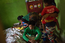 April 27, 2014 - Sanca, Indonesia. While working in Saudi Arabia as a domestic worker, Tati was beaten by her employer and is now paralysed. While confined to her bed she is cared for by Carla, her husband.  © Nicolas Axelrod / Ruom