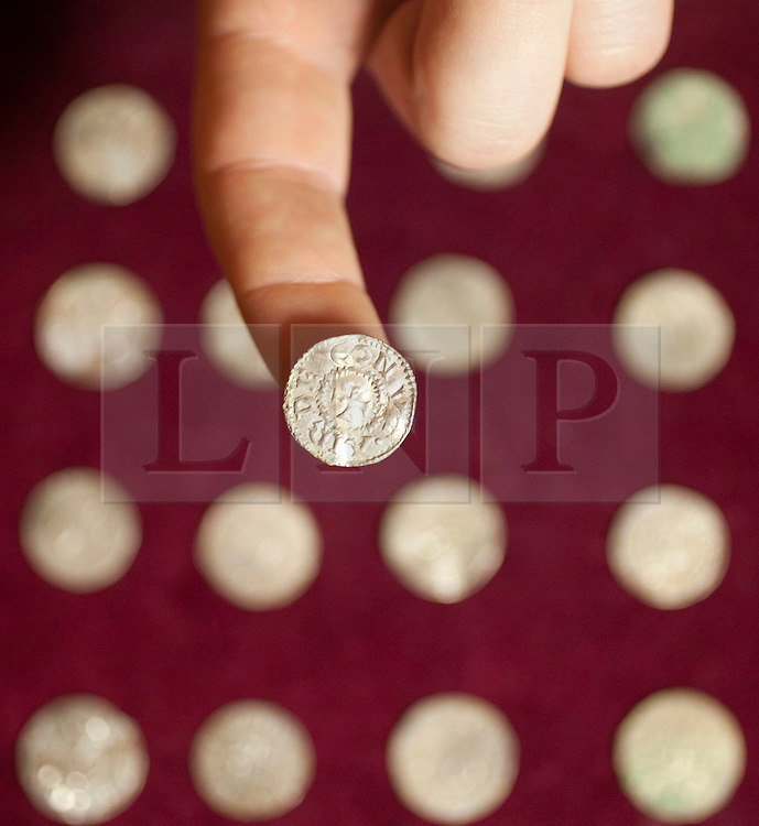© Licensed to London News Pictures. 14/12/2011. LONDON, UK. A member of staff from the British Museum holds a coin carrying the name of an otherwise unknown Viking ruler from the north of England. The coin, part of the Silverdale Viking Hoard discovered in September 2011 in Lancashire, was shown as part of the an exhibition at the museum highlighting the importance of the Treasure Act and Portable Antiquities Scheme and includes valuable finds from across the country. Photo credit: Matt Cetti-Roberts/LNP