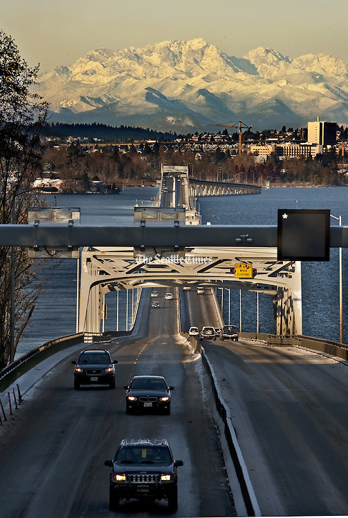 The snow-capped Olympic Mountains loom behind the 520 Bridge over Lake Washington. <br />