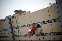 Aug 17, 2011:  A NYC Corrections Department Salt Spreader dangles 3 stories high after it crashed though a wall at 58-65 52nd Rd in Queens, the site of a NYC Sanitation Department equipment repair facility. According to reports at the scene, the operator was trapped in the cab of the vehicle and went in and out of consciousness for a period of time before being rescued by FDNY personnel. The cause of the crash is under investigation. Credit: Rob Bennett for The Wall Street Journal