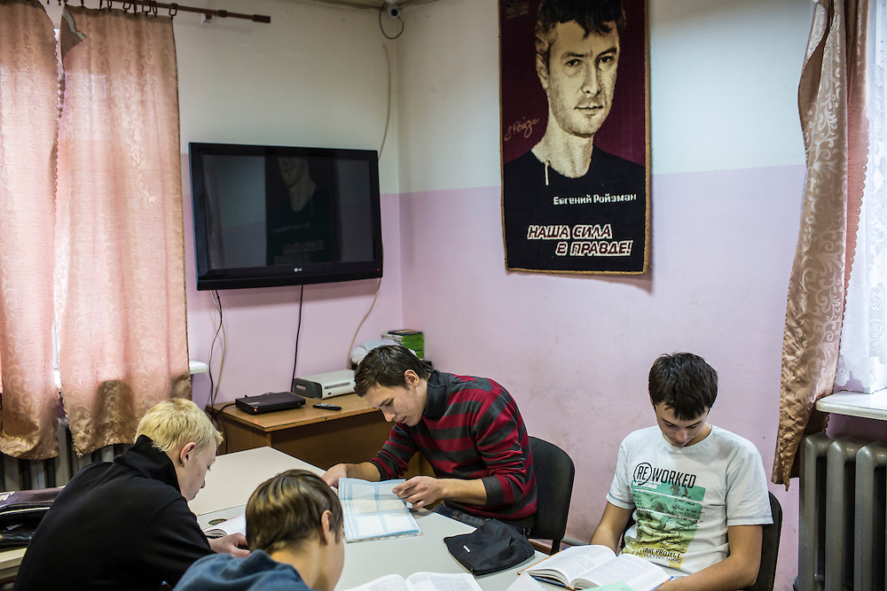 YEKATERINBURG, RUSSIA - OCTOBER 16: Teenage boys who live at a facility run by City Without Drugs for at-risk youth do their homework underneath a picture of founder Yevgeny Roizman on October 16, 2013 in Yekaterinburg, Russia. Nine boys, many of whom were either experimenting with drugs or had dropped out of school, live at the group home, where school attendance and homework are mandatory. City Without Drugs is a well-known narcotics treatment program in Russia founded by Yevgeny Roizman, who was elected mayor of Yekaterinburg in September 2013. (Photo by Brendan Hoffman/Getty Images) *** Local Caption ***
