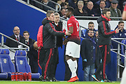 Kieran Mckenna first team coach and Manchester United interim Manager Ole Gunnar Solskjaer offer advice to Manchester United Midfielder Paul Pogba during the Premier League match between Cardiff City and Manchester United at the Cardiff City Stadium, Cardiff, Wales on 22 December 2018.