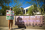 25 JUNE 2012 - PHOENIX, AZ:   ATLI MEXITA stands next to a banner she placed in front of the Immigration and Customs Enforcement (ICE) offices in central Phoenix Monday. About 100 immigration supporters held a protest against ICE and continued deportations by the Obama administration. Protesters also celebrated the US Supreme Court decision to overturn most of SB1070, Arizona's tough anti-immigration law.   PHOTO BY JACK KURTZ