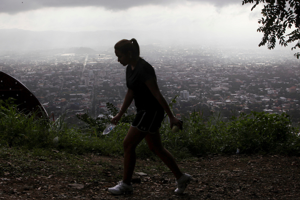 In this March 10, 2012 photo, a woman walks in a park that overlooks San Pedro Sula, Honduras. A wave of violence has made Honduras among the most dangerous places on Earth, with a homicide rate roughly 20 times that of the U.S. rate, according to a 2011 United Nations report.