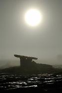 Sunrise moonrise in fog over Poulnabrone prehistoric Stone Age dolmen tomb. The Burren limestone plateau, County Clare, Ireland