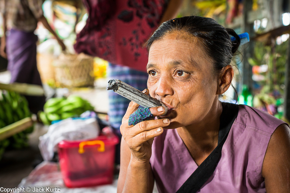 08 JUNE 2014 - YANGON, MYANMAR: A woman smokes a home made cheroot on a steamer sailing up the Yangon River. Yangon, Myanmar (Rangoon, Burma). Yangon, with a population of over five million, continues to be the country's largest city and the most important commercial center.      PHOTO BY JACK KURTZ