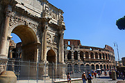The Arch of Constantine, a triumphal, or victory arch in Rome. It is positioned between the Collosseum and the Palatine Hill. It commemorates Emperor Constantine's victory in the Battle of Milvian Bridge in the early 4th century AD. It was dedicated in 315 AD and features reliefs/friezes documenting previous Emperors and victory figures. The Collosseum is shown here in the background.