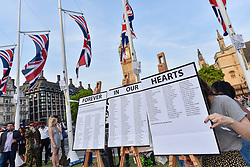 © Licensed to London News Pictures. 19/06/2017. London, UK.  The names of the victims and survivors are displayed as people gather for a vigil in Parliament Square to remember those who died in the Grenfell Tower fire in North Kensington of 14 June.  Mourners and wellwishers were given the opportunity to speak and to write messages on a community banner.  Photo credit : Stephen Chung/LNP