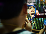 25 SEPTEMBER 2016 - BANGKOK, THAILAND: Likay performers put on their makeup and costumes before a Likay performance in Pom Mahakan Fort. The performance was to support residents of the old fort  who are fighting eviction orders by the city of Bangkok. City officials have made repeated attempts to evict people since Sept 3, 2016, but about 44 families are still living in the community. Likay is a form of popular folk theatre from Thailand. It uses a combination of extravagant costumes, barely equipped stages and vague storylines. The performances depend mainly on the actors' skills of improvisation and the audiences' imagination. There used to be several Likay troupes based in the old fort, but they left the community more than 50 years ago. The troupe that performed Sunday night was an amateur troupe comprised of college students and office workers.      PHOTO BY JACK KURTZ