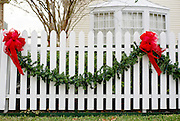 Garland and ribbons hang on a white picket fence for the holidays.