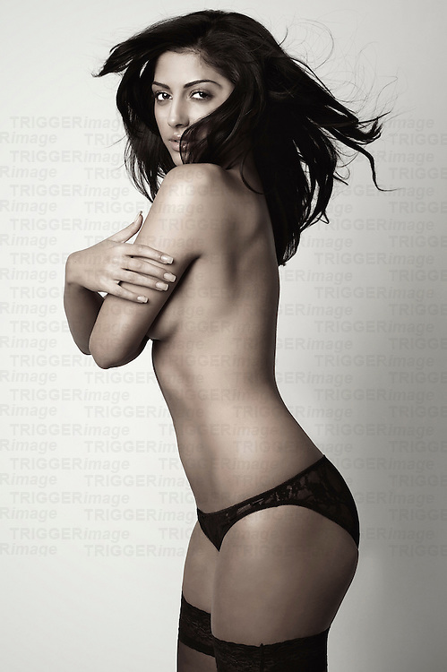 A young woman with dark hair topless with arms crossed