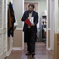 Dennis Farris Jr., walks from the filing room to the court room as he looks over a case file in municipal court in Tupelo Thursday.