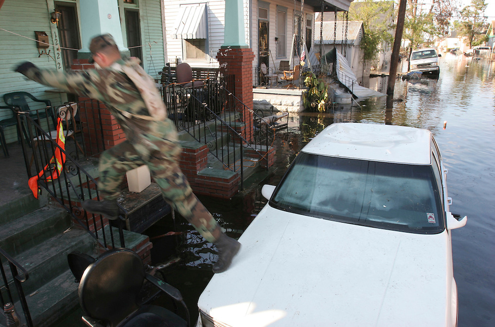 PFC Donald Epperson and other soldiers use any means possible to get to the frfont door from their Humvee without touching the filthy, contaminated water while searching for survivors in the flooded homes of New Orleans. Oregon National Guard troops work in New Orleans after the wrath of Hurricane Katrina. Photographed September 8, 2005. (Thomas Patterson / Statesman Journal)