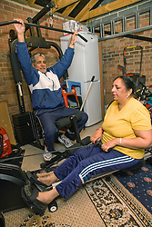 Older woman exercising on a rowing machine whilst her husband uses lat pull down equipment in their home gym,