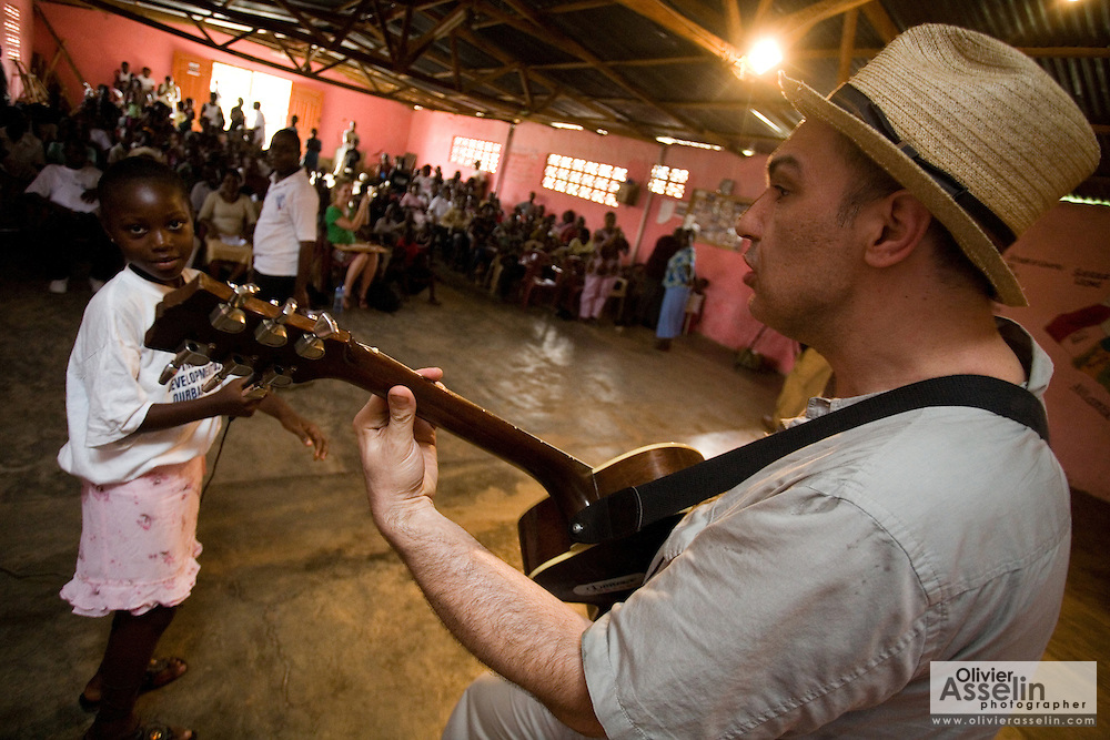 Canadian artist Dave Bidini plays a song during a performance by the Liberian Dance Troupe (LDT) at the Buduburam refugee settlement, roughly 20 km west of Accra, Ghana's capital, on Saturday April 14, 2007. One of the main goals of the LDT is to teach young refugee children, many of which have never seen Liberia, about their country's music, dance and culture. The Buduburam refugee settlement is still home over 30,000 Liberians, most of which have mixed feelings about returning to Liberia..