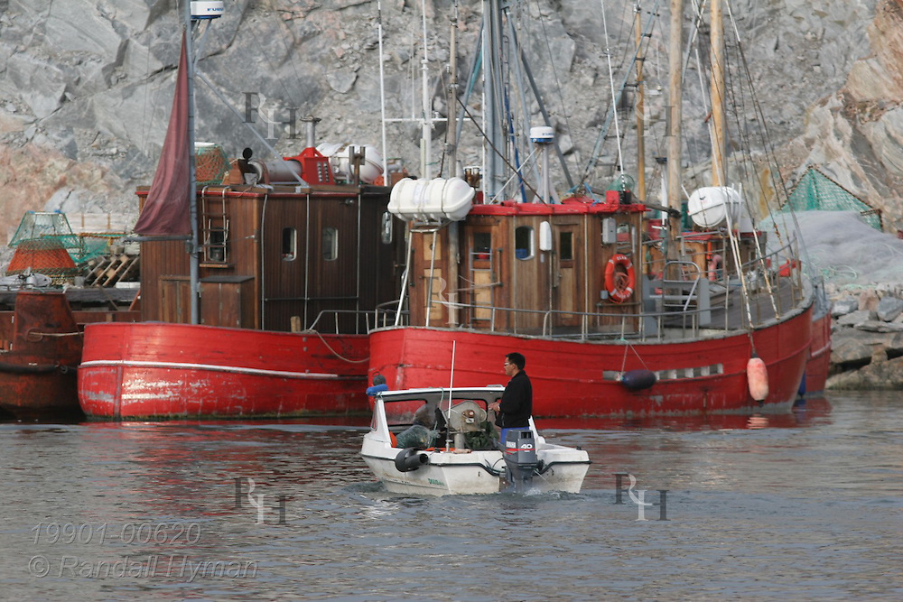 Local man pilots motorboat past several small fishing boats in harbor at Ilulissat, third largest town in Greenland.