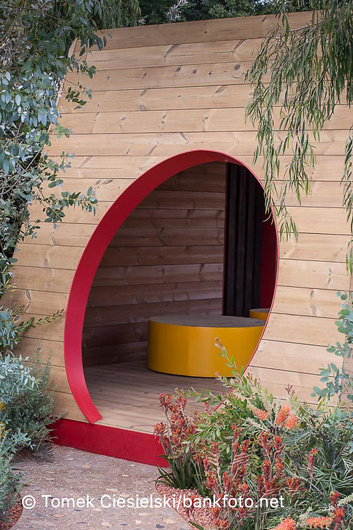 Modern geometricasl bower with oval entrance located between australian plants