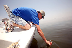 28 May 2010. Barataria Bay to Grand Isle, Jefferson/Lafourche Parish, Louisiana. <br /> Louisiana born and raised Justin Workmon collects an oil sample from the eerily empty ocean where water that would ordinarily be crystal clear but is now gravy coloured thanks to dispersed oil just off Grand Terre Island where Barataria Bay meets the Gulf of Mexico. Ordinarily the ocean would be filled with shrimp boats, sport fishermen, and sea birds, especially in the run up to memorial day weekend. The ecological and economic impact are devastating to the region. Oil from the Deepwater Horizon catastrophe is evading booms laid out to stop it thanks in part to the dispersants which means the oil travels at every depth of the Gulf and washes ashore wherever the current carries it. The Louisiana wetlands produce over 30% of America's seafood and are the most fertile of their kind in the world.<br /> Photo credit; Charlie Varley<br /> www.varleypix.com