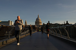 © London News Pictures. 03/04/15. London, UK. Commuters cross over the Millenium Bridge duirng sunrise, City of London. Photo credit: Laura Lean/LNP