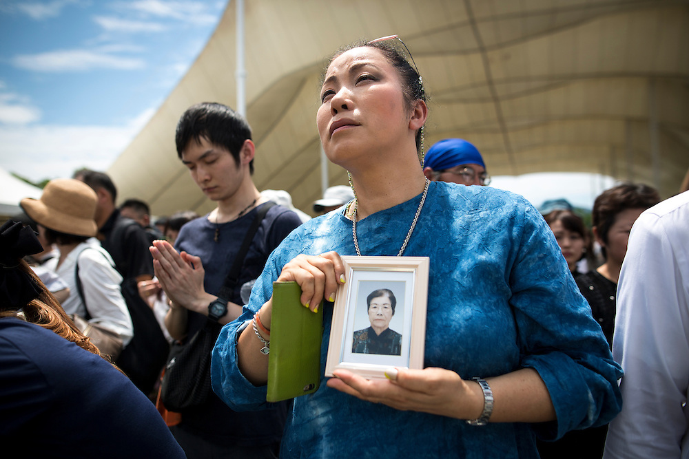 NAGASAKI, JAPAN - AUGUST 9 : A woman holding a photograph pray for the atomic bomb victims in front of the Peace Statue in Nagasaki Peace Park, Nagasaki, southern Japan, Tuesday, August 9, 2016. Japan marked the 71st anniversary of the atomic bombing on Nagasaki. On August 9, 1945, during World War II, the United States dropped the second Atomic bomb on Nagasaki city, killing an estimated 40,000 people which ended World War II. (Photo by Richard Atrero de Guzman/NURPhoto)