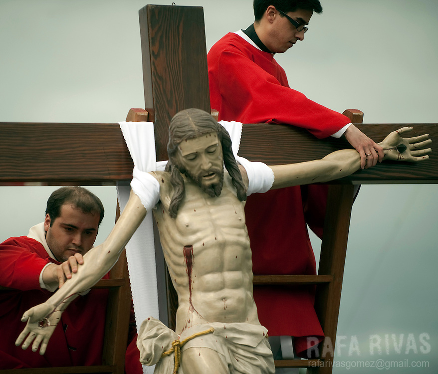 Two priests remove remove nails from the hands of a Christ figure before descending it from the cross, during the Holy Friday procession in the Northwestern Spanish village of Bercianos de Aliste, during the Holy Week of Zamora province, on April 22, 2011.