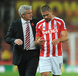 Stoke Manager, Mark Hughes consults a disappointed Stoke's Jonathan Walters at the end of the game - Photo mandatory by-line: Dougie Allward/JMP - Mobile: 07966 386802 - 29/10/2014 - SPORT - Football - Stoke - Britannia Stadium - Stoke City v Southampton - Capital One Cup - Fourth Round