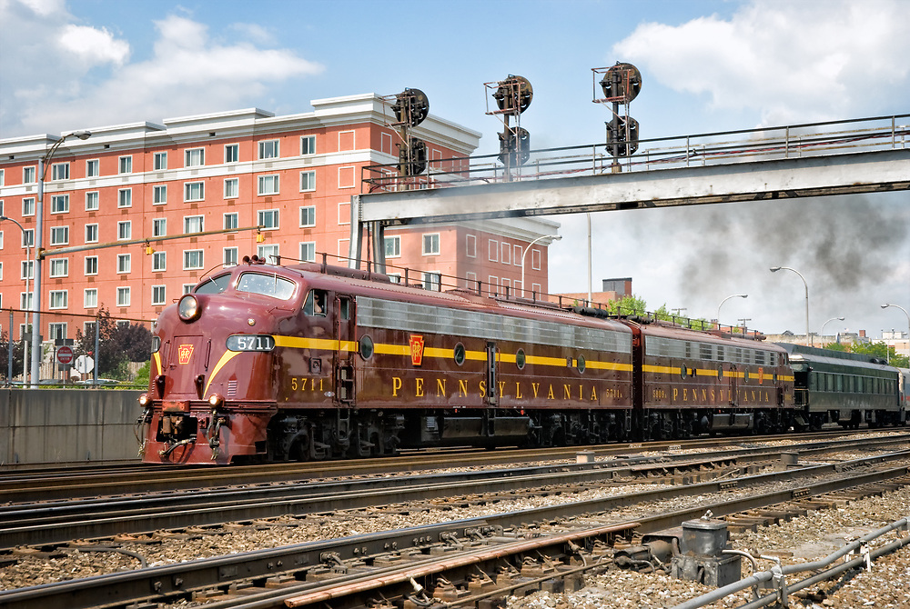 These beautiful railroad locomotives have been restored to their original appearance and road number when they were new on the Pennsylvania Railroad back in 1952. Today, they are privately owned by the Juniata Terminal Company who also did the full end-to-end restoration and they are based out of their facility in Philadelphia. They are often run on excursions and at quite a few special functions commemorating railroad history as they are here, running at Altoona PA&rsquo;s annual Railfest.<br /> <br /> These locomotives were built by the EMD section of General Motors; this model is known as an E8 and sometimes nicknamed &ldquo;bulldogs&rdquo; or &ldquo;covered wagons&rdquo; by the crews. Designed for high-powered high-speed passenger service, each one has two diesel engines inside that make a total of 2250 horsepower by powering DC electric traction motors with generators, which was a lot back in the day. At this showing in Altoona where they were giving rides on the train up around the Horseshoe Curve and back, two of these 60 year old engines paired had plenty of power to simply walk away with a very heavy and long train of vintage passenger cars. Passenger cars from that era had bodies made of steel and floors of thick concrete to make for a smooth ride, and their weight was considerable.<br /> <br /> I spoke with an engineer a few years after this image was taken who had run this pair pulling an excursion on the New York to DC corridor. The marked speed for that section of mainline is 100 mph, but he claimed to have run these locomotives up to 110 for a little stretch, just to see how they&rsquo;d do. Naturally, I asked him how it went and the reply was &rdquo;smooth as glass&rdquo;&hellip;<br /> <br /> In this scene, this pair are pulling away from the Altoona station with that heavy passenger train to begin the climb up the mountains. While idling a long time waiting for departure, diesel fuel has built up in the cylinders so when the throttle is notched open