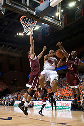 Virginia Cavaliers guard J.R. Reynolds (2) leaps around Virginia Tech Hokies guard Zabian Dowdell (1) and Virginia Tech Hokies forward Deron Washington (13) on his way to the basket.  The Virginia Cavaliers Men's Basketball Team defeated the Virginia Tech Hokies 69-56 at the John Paul Jones Arena in Charlottesville, VA on March 1, 2007.
