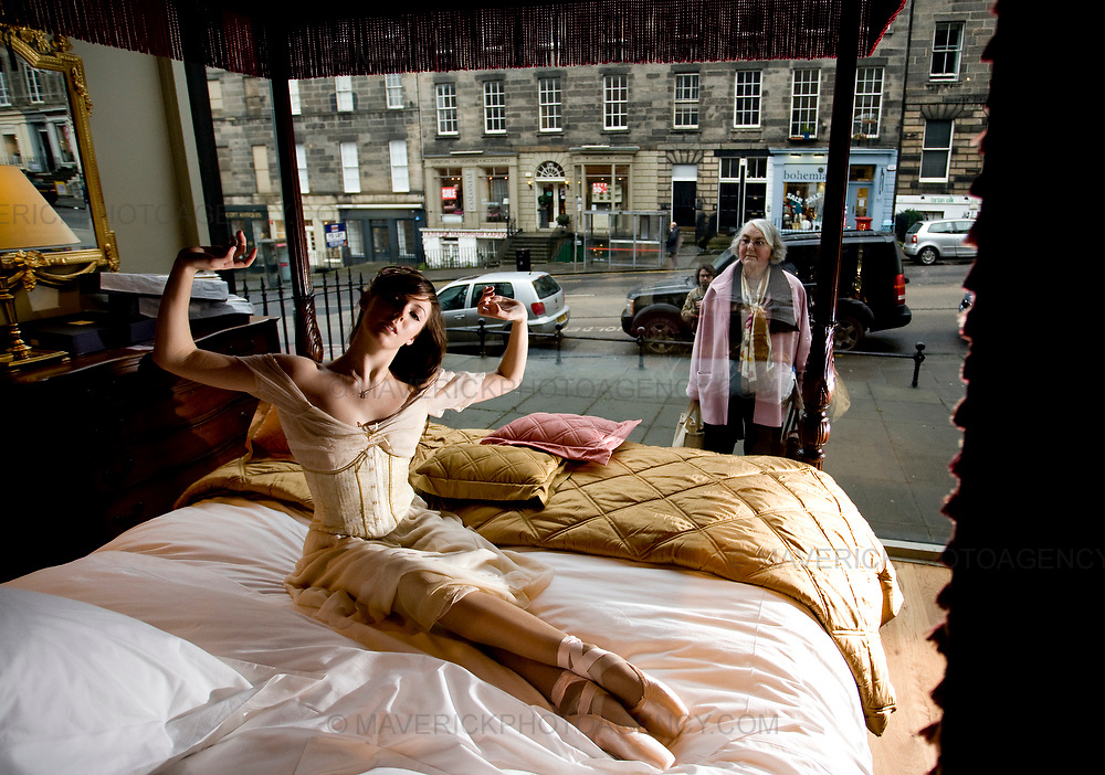 """A shopper looks through a bed shop window as Scottish Ballet dancer Lauren Bryden wakes up, dressed in character as Princess Aurora from the the news scottish ballet production """"The Sleeping Beauty""""..7/1/2009.Picture Michael Hughes/Maverick"""