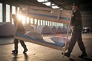 Notunterkunft für Flüchtlinge im ehemaligen Flughafen Berlin Tempelhof. Soldaten der Bundewehr und Helfer des THW und der Berliner Feuerwehr bauen in einem Hanger des früheren Flughafengebäudes Stockbetten auf.