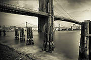 Black and white sepia photography of the Brooklyn Bridge taken with a long exposure in Downtown Manhattan, New York