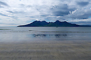 The stunningly beautiful Isle of Rum reflected in the receeding tidal waters on the beach of Traigh Chlithe, Laig Bay, Isle of Eigg under a dramatic, stormy sky.<br /> <br /> The Rum peaks are from left to right: Sgurr nan Gillean, Ainshval, Trollabhal (Trollaval), Bienn nan Stac, Askival & Hallival (Allival).   <br /> <br /> Date taken: 12 June 2016.