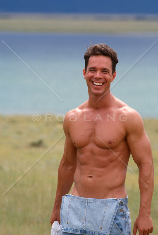 Muscular shirtless man smiling by a lake in New Mexico