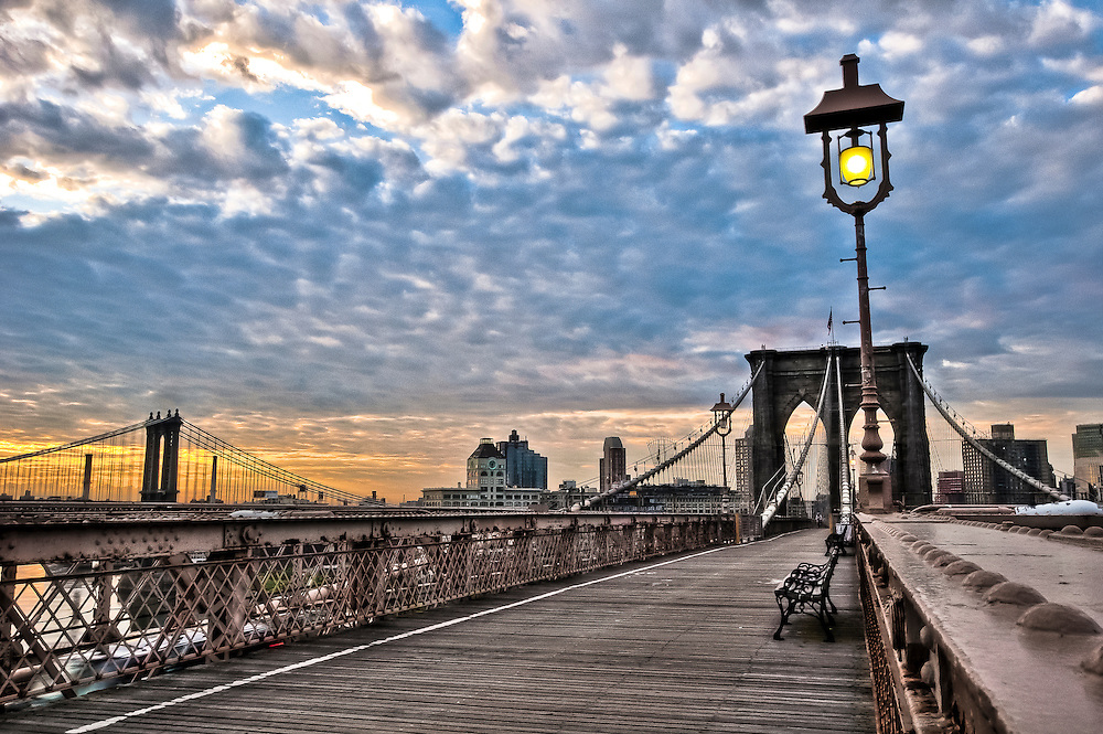 Lantern lighted on the Brooklyn Bridge at sunrise. The Clock Tower in DUMBO, Brooklyn, is sighted in the background, New Yrok, 2010.