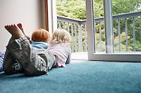 Sisters (3-6) lying on carpet looking through balcony door