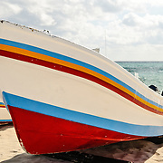 A brightly painted boat pulled up on the sandy beach at Playa del Carmen on Mexico's Yucatan Peninsula.