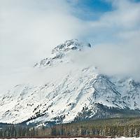 modern woman skiing across frozen lake two medicine lake winter glacier national park, montana