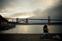 A little girl holds a hot beverage on the dock at Crissy Field, San Francisco, California, USA.