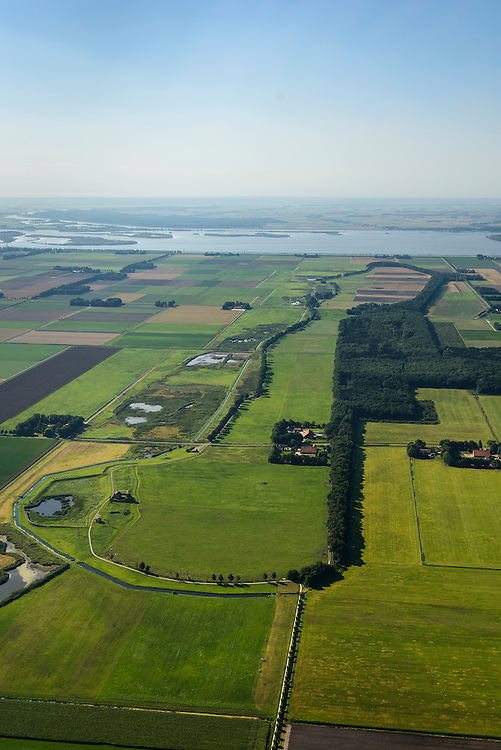 Nederland, Noordoostpolder, Schokland, 27-08-2013. Dorp en voormalig eiland in de Zuiderzee. Gezien vanuit het Noorden met links voormalige haven en vuurtoren, lichtwachterswoning. Onderdeel van de UNESCO Werelderfgoedlijst. <br /> Het verlagen van de grondwaterspiegel in de Noordoostpolder leidt tot inklinking waardoor het eiland steeds lager komt te liggen. Om verder wegzinken te voorkomen een hydrologische zone aangelegd<br /> Village and former island, seen from the north with on the left the former harbor and lighthouse, light house keeper residence. Part of the UNESCO World Heritage List. Lowering the groundwater level in the Noordoostpolder leads to subsidence and causes the island the sink away. In order to prevent further decline a hydrological zone has been created.<br /> luchtfoto (toeslag op standaard tarieven);<br /> aerial photo (additional fee required);<br /> copyright foto/photo Siebe Swart.