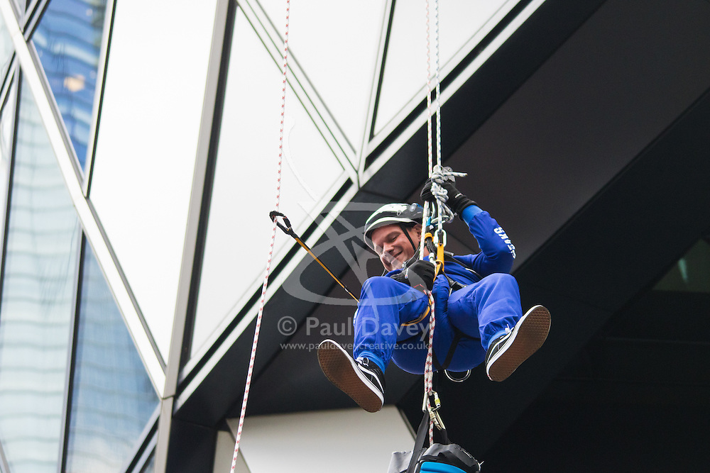 London, September 7th 2015. PICTURED: Down at last! Alistair McAuley of AkzoNobel completes his abseil down the side of 30 St Mary's Axe - The Gerkhin. The Outward Bound Trust City Three Peaks Challenge in conjunction with The Royal Navy and Royal Marines Charity is a breathtaking abseiling endeavour on the greatest urban mountain range: The City of London.