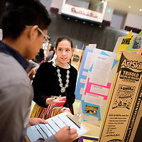 Devin Fatt, left, listen as Lillian Campbell of <br /> Lukachukai Community School describes her project on Din&egrave; Ovens: Cooking With Wood during the 2018 Navajo Nation Science Fair at Red Rock Park Thursday.