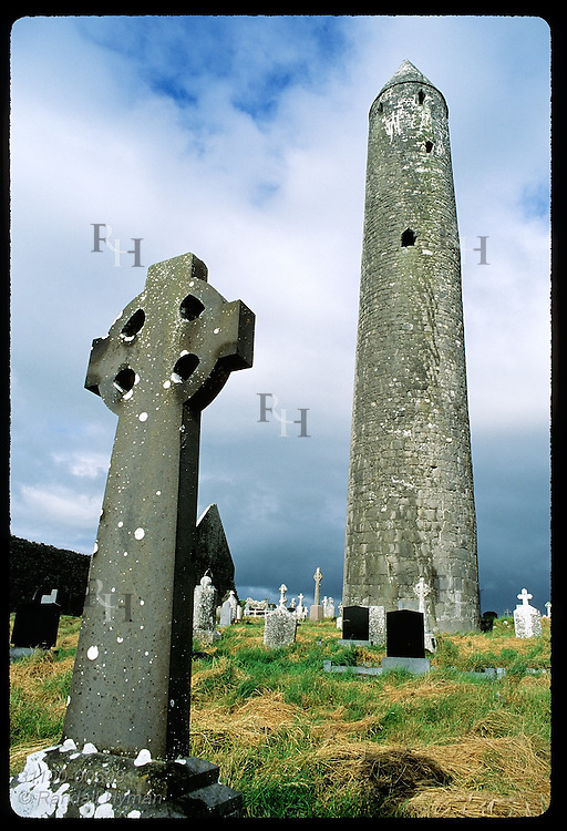 Kilmacduagh round tower (112') looms behind Celtic cross at St Colman monastery site; Gort. Ireland