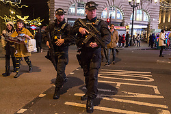 London, December 31 2017. Armed police at Piccadilly Circus patrol as revellers in London's West End enjoy the build-up to New Year. © SWNS