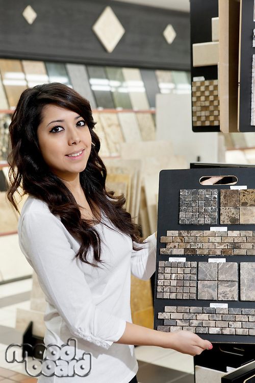 Portrait of a happy young owner showing sample tiles in store