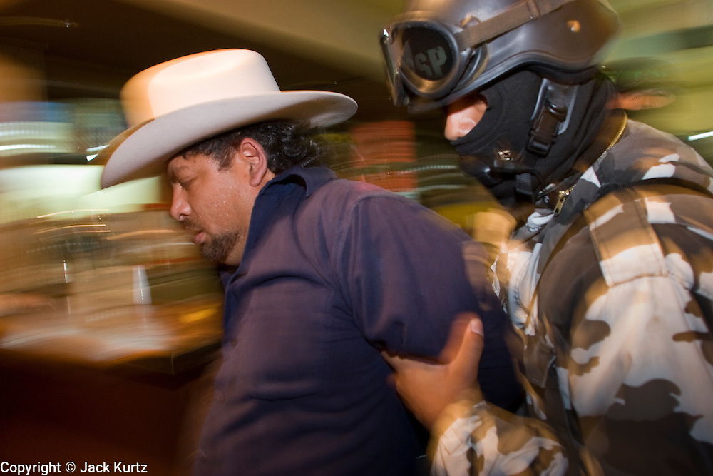 "05 FEBRUARY 2005 - NOGALES, SONORA, MEXICO: A Nogales, Mexico, police officer arrests a man in a bar during an anti-gang sweep. Members of ""Grupo Operativos"" a special operations unit of the Nogales, Sonora, Mexico, police department, on patrol in Nogales, Saturday night, Feb. 5. The Operativos specialize in anti-gang enforcement and drug interdiction missions. In recent months they have stepped up patrol activity in Nogales communities near the border. In January 2005, the US Department of State has issued a travel advisory advising US citizens to avoid travel along the US Mexican border because of increased violence, including the kidnapping of US citizens, in border communities. Most of the violence has been linked to the drug cartels, who are increasingly powerful in Mexico. The Operativos also patrol the districts of Nogales frequented by US tourists in an effort to prevent crime directed against US citizens.   PHOTO BY JACK KURTZ"