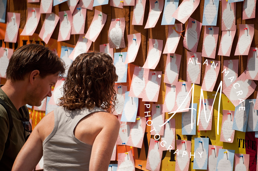 "A couple look at notes on a ""love wall"", one of several about the grounds at Gunstock Mountain Resort during the annual Soulfest on Saturday, August 7, 2010.  (Alan MacRae/for the Citizen)"